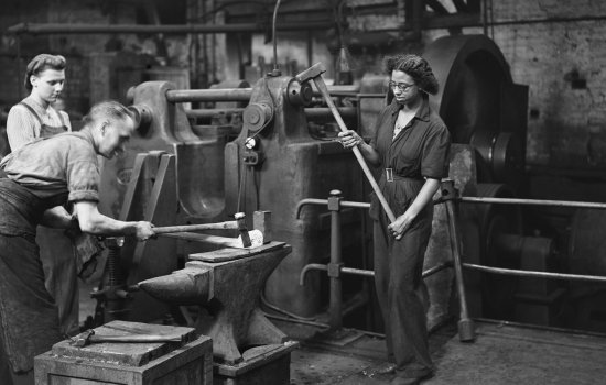 Women workers assisting a blacksmith in the forge at the London & North Eastern Railway's Doncaster railway works, 14 August 1943.