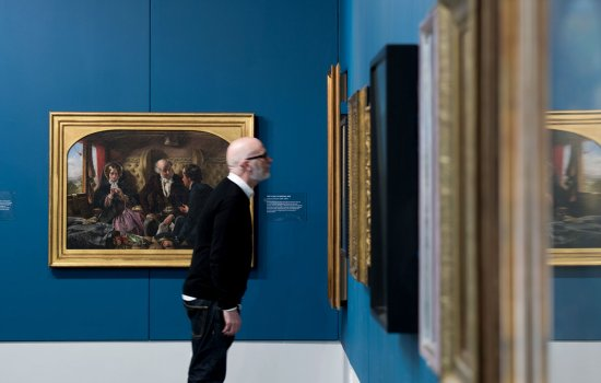 A visitor takes a closer look at the paintings in the Highlights exhibition