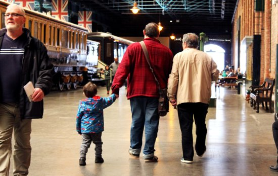 Men and a boy walk through station hall