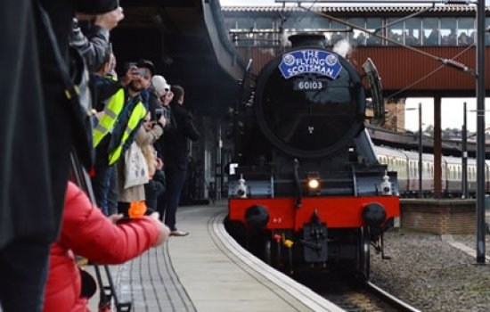 Flying Scotsman arriving into a station as people wait on the platform