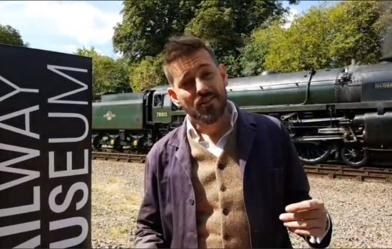 Tim Dunn stands in front of locomotive Oliver Cromwell