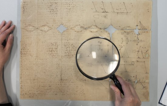 A magnifying glass is used to read an old document