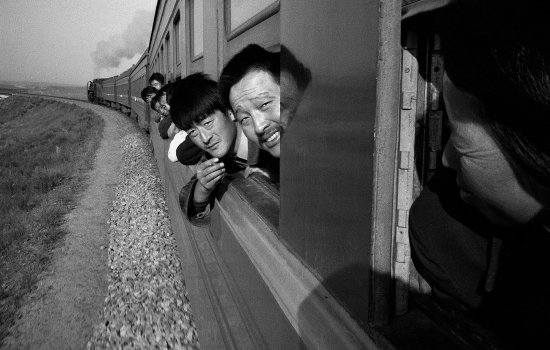 Men stick their heads out of the carriage window