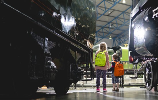 Children with backpacks stand next to huge locomotives