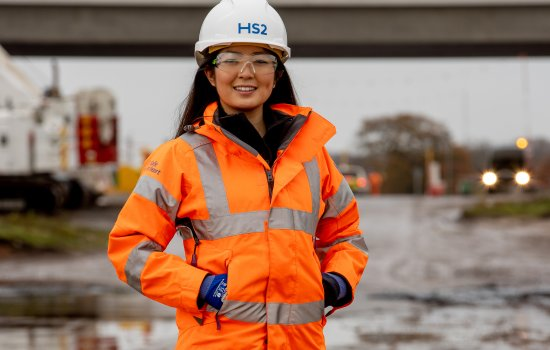 Lin Qi in orange hi-vis standing on a construction site