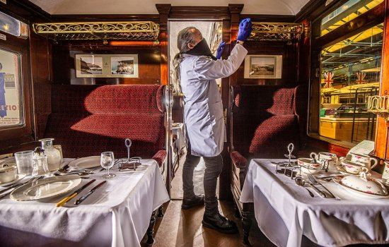 A white man in a white coat and blue nitrile gloves cleans a historic railway dining carriage
