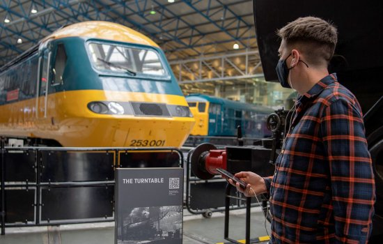 A white man looks at a yellow and blue locomotive in a large hall. He holds a smartphone connected to his earbud headphones.