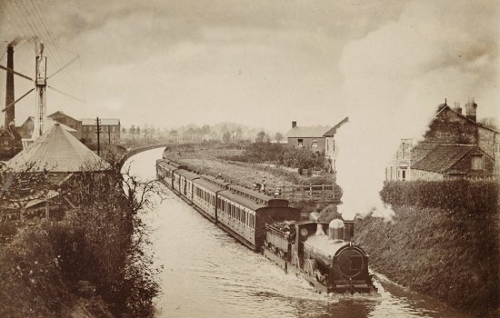 A train half-submerged in floodwater, with the engine billowing smoke as it travels