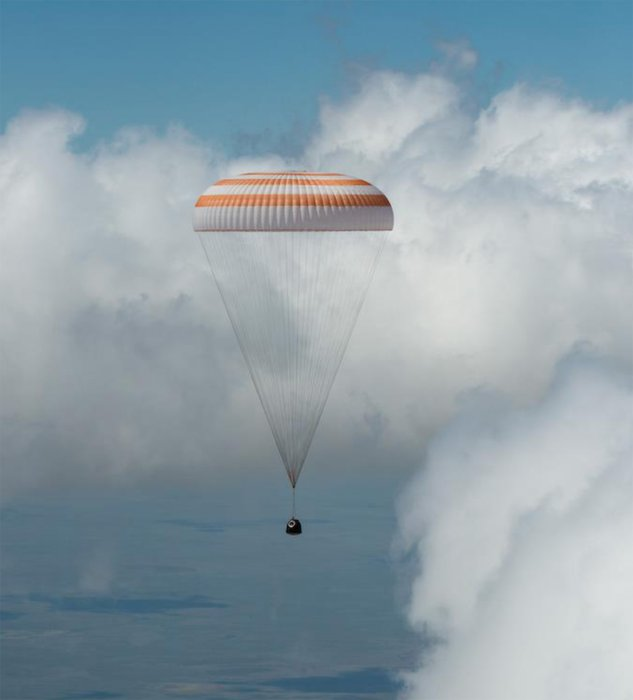 The Soyuz descent module with parachute attached, coming in to land