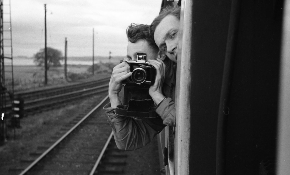 Black and white photograph of a man leaning out of a train window holding a camera