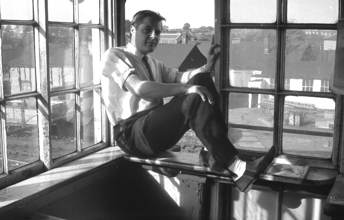 Black and white photograph of a man sitting in the window of a signalling box