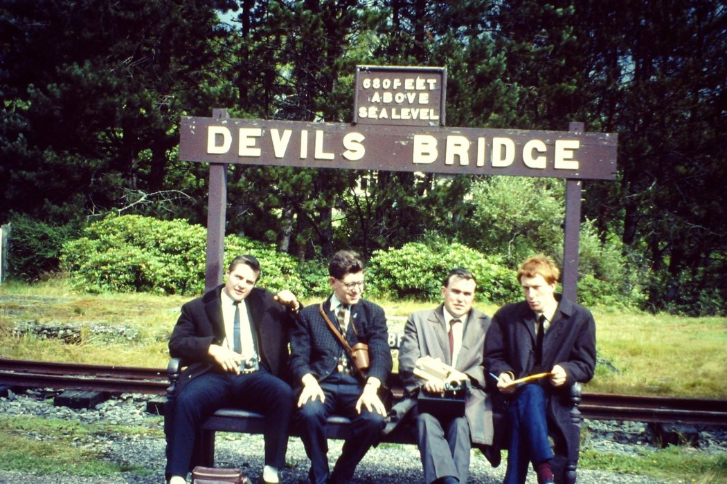 Colour photograph of a group of schoolboys sitting in front of a sign reading 'Devils Bridge'