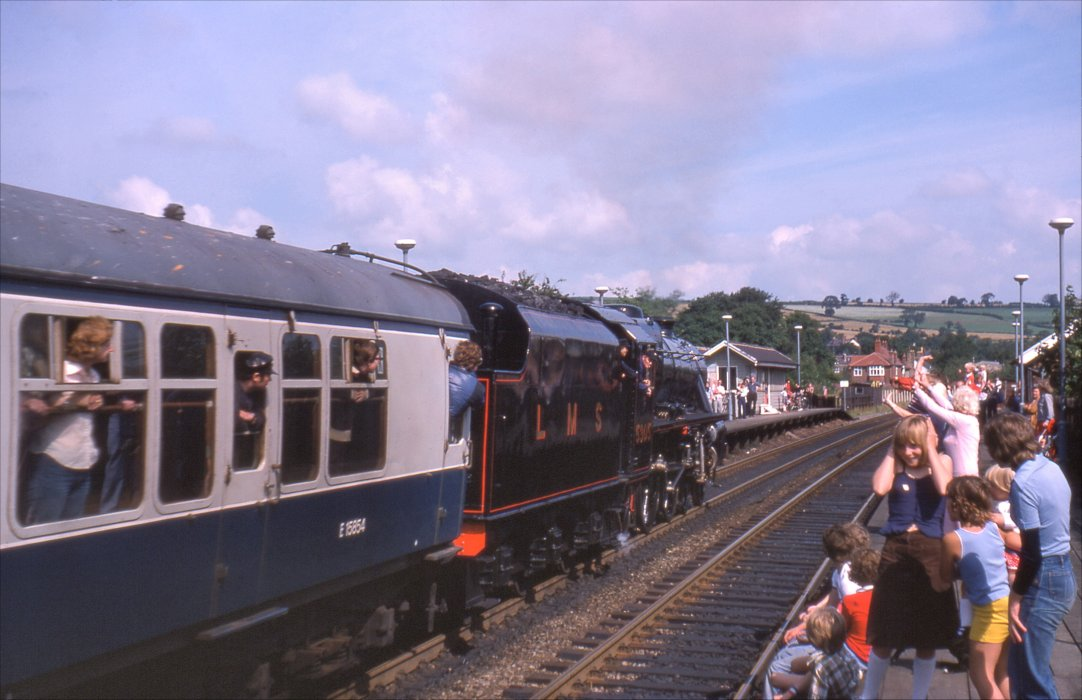Colour photograph of crowds waving at a passing train