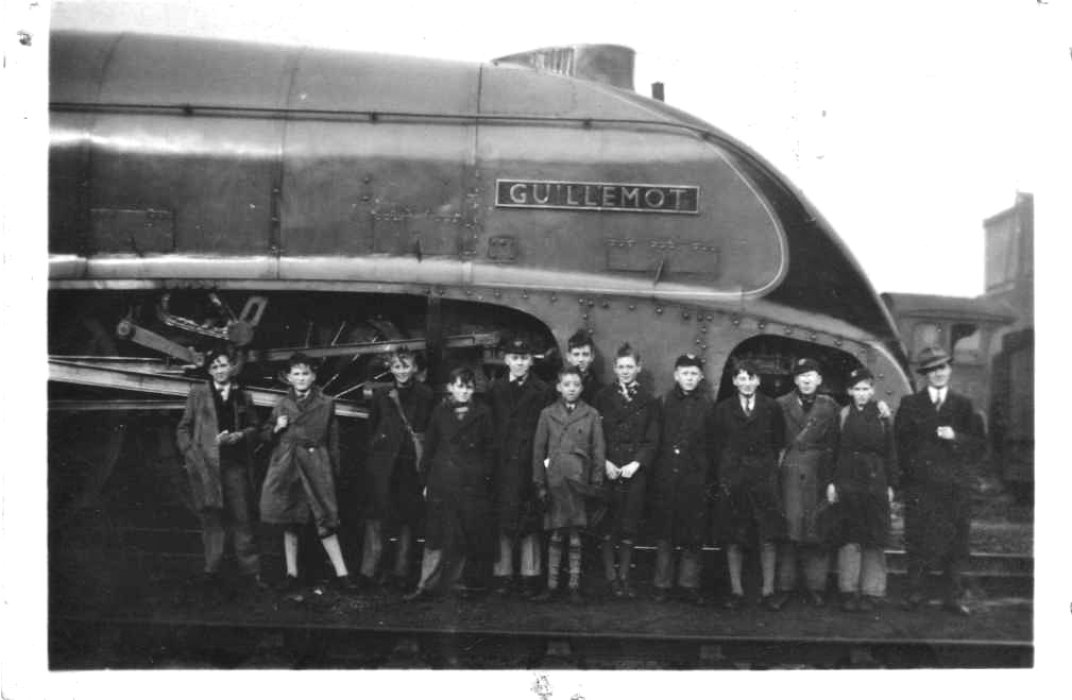 "Black and white image of a group of boys standing next to the locomotive Gresley A4 60020 ""Guillemot"""