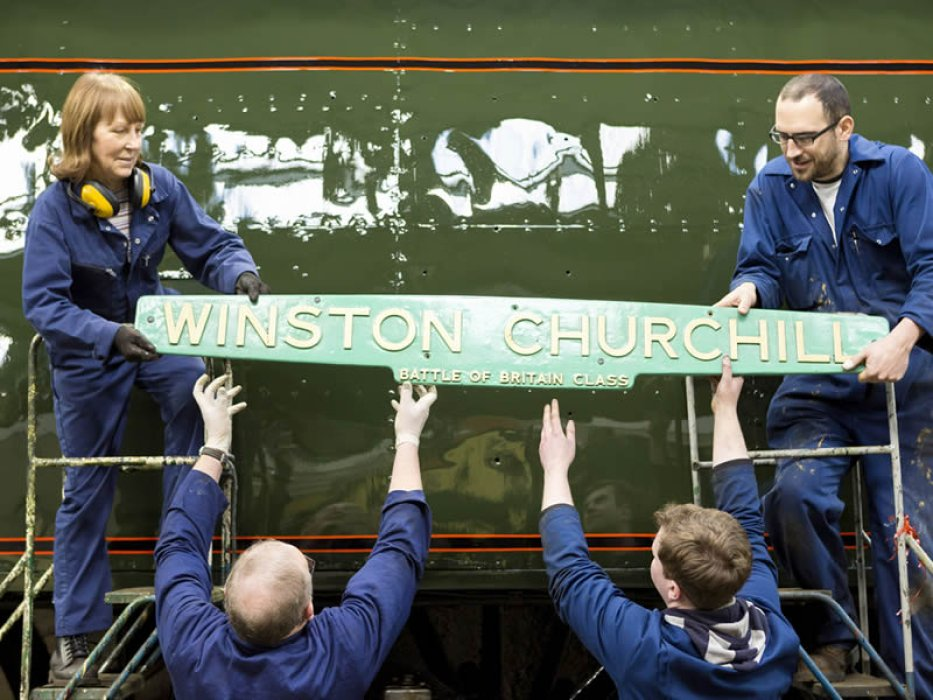 Great care is taken as the repainted nameplate is offered up to the locomotive's side for fixing