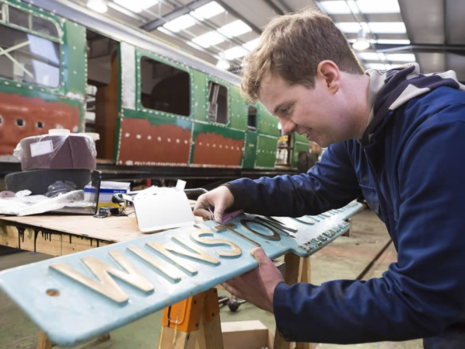 Mid Hants Railway painter Ollie examines the locomotive's nameplate