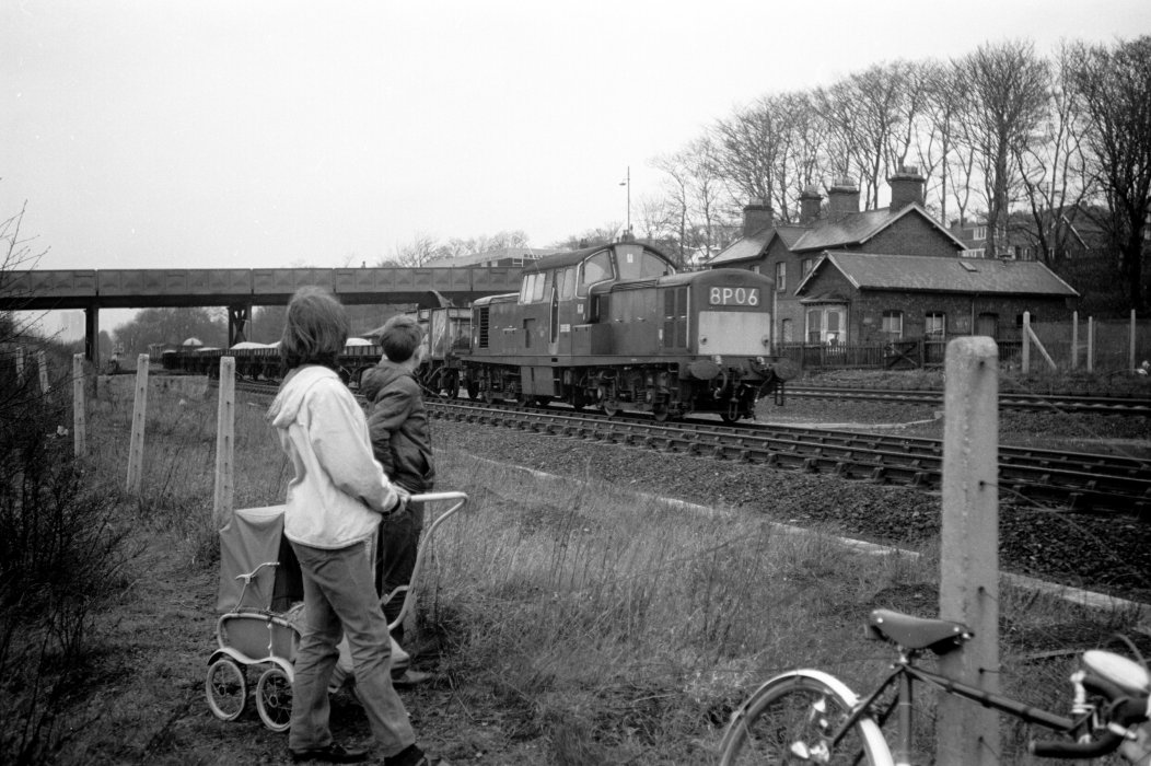Black and white image of a girl and boy watching a train go by