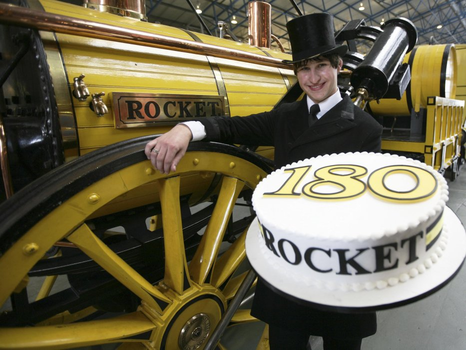 An actor dressed as Robert Stephenson holds a cake and stands next to a replica Rocket locomotive