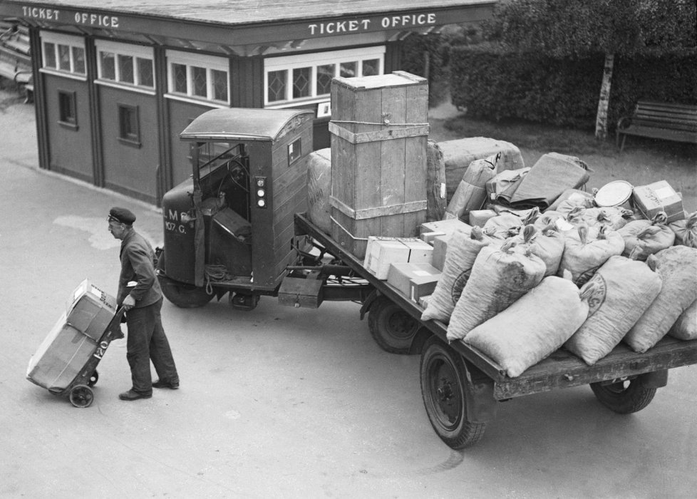 A man unloads goods from a flatbed vehicle