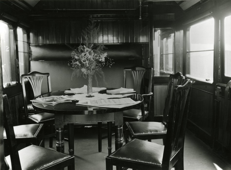 Ambulance train no. 24, Lancashire & Yorkshire Railway. The officers' mess, with six chairs round a circular wooden table with a vase of flowers and papers