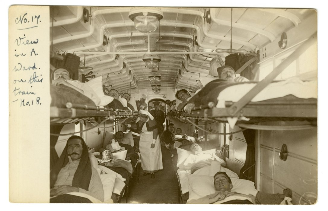 View in a ward car on an ambulance train, with injured soldiers lying in three-tier bunks