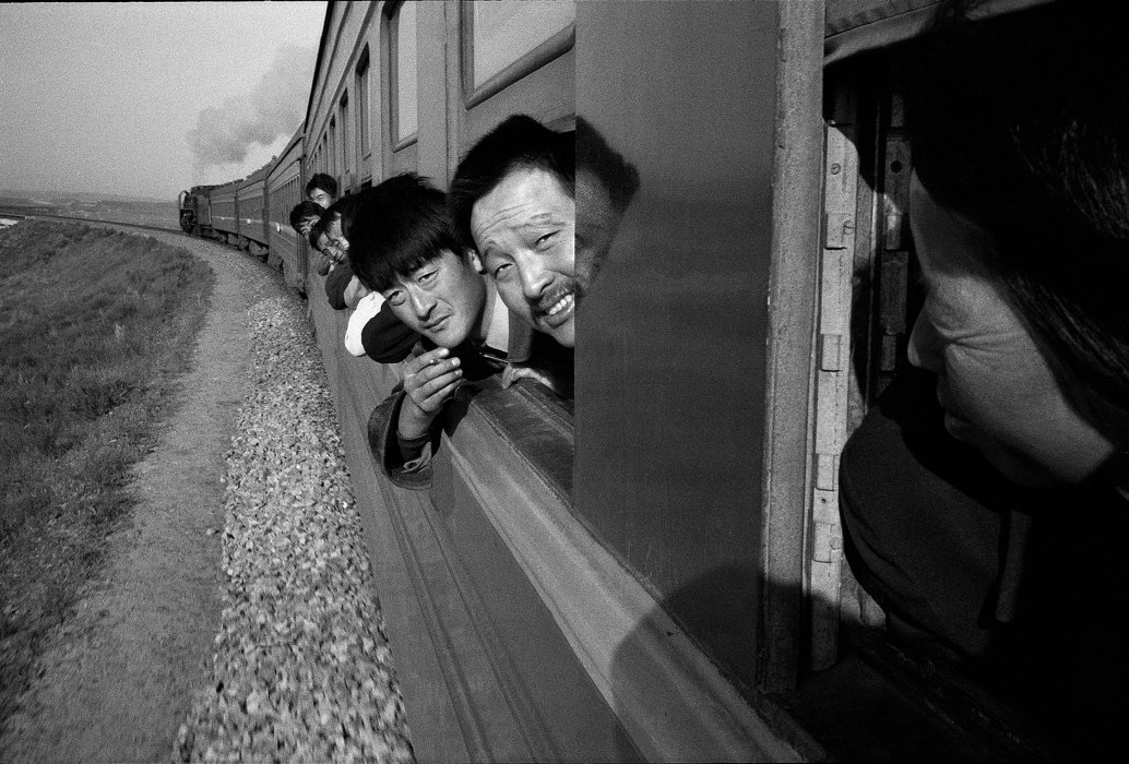 Passengers look out the window of a steam-hauled train